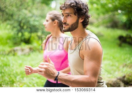 Couple running in a park. Shallow depth of field, focus on the man