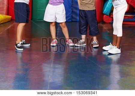 Many legs with shoes of different children in a gym