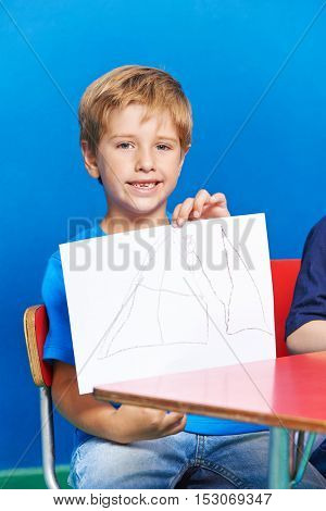 Happy boy showing his drawing in kindergarten at table