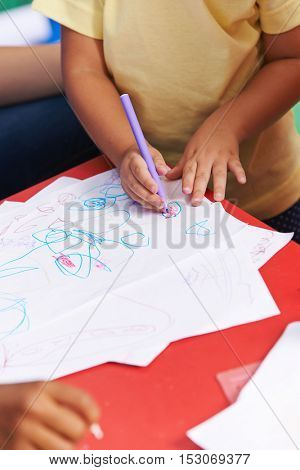 Hands of child painting on a piece of paper with a felt pen in kindergarten
