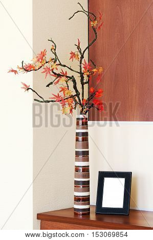 Autumn arrangement in a vase on the table and photoframe with place for your foto.