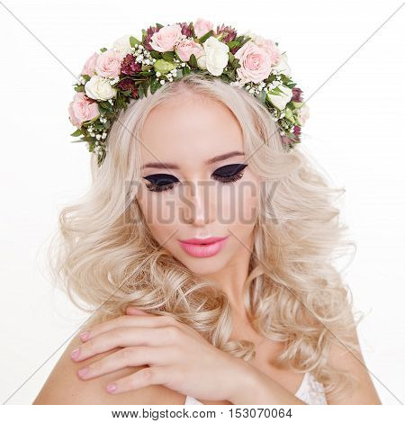 Fashion shot of a stunning young woman posing in white dress over white background. Bright makeup. Eye-lines. Beauty, fashion. Floral