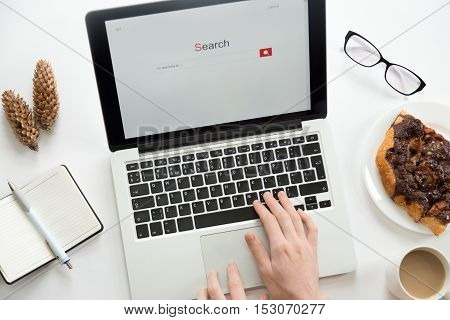 Hands working on a laptop, glasses, notebook, cones, office supplies, mug and a piece of pie on the plate. Business concept, high angle