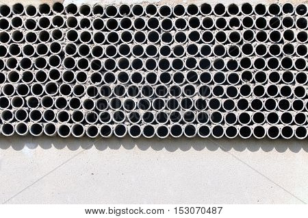 Industrial background. Texture of many pipes with holes on a white wall.