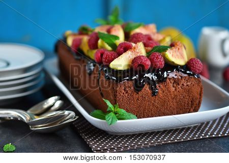 Chocolate cake with raspberries figs peaches and chocolate. Selective focus.