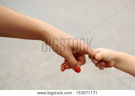 Little fragile baby hand holding mothers finger on gray background