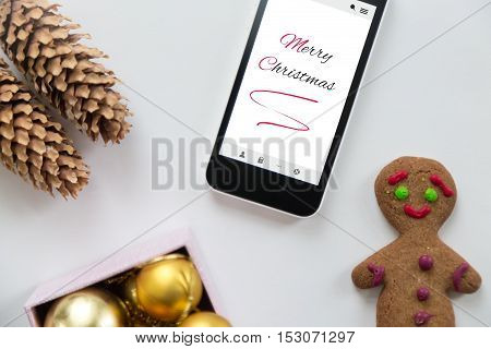 Flat view of a phone among cute Christmas decoration, cones, box of glass balls, ginger man. Christmas concept, high angle, closeup