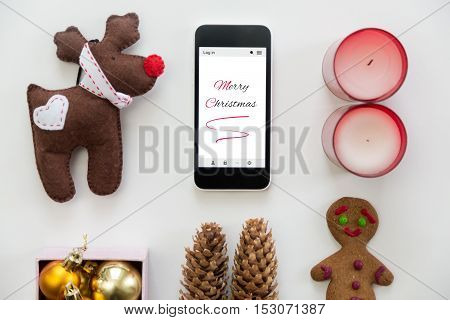 Flat view of mobile phone in the centre of cute Christmas decoration, cones, box of glass balls, ginger man, candles, Rudolph the Red Nosed Reindeer toy. Christmas concept, high angle