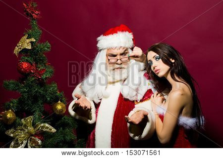 Pretty girl in sexy red dress touches eyeglasses of santa claus man with white beard in xmas suit near Christmas tree