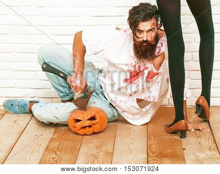 Bearded zombie man with beard vampire or bloody war soldier with wounds and red blood with halloween pumpkin and axe sits near female slim legs on wooden floor