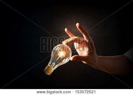 Hand pointing light bulb . Mixed media