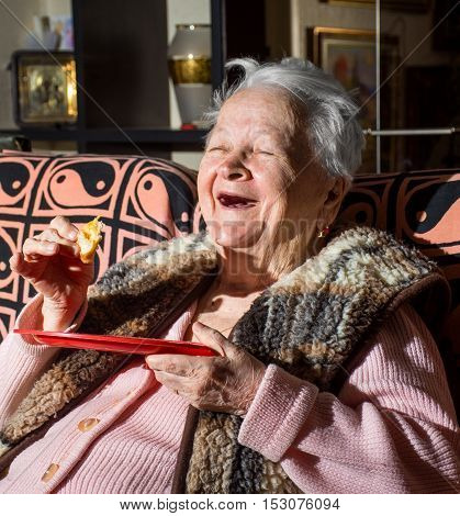 Old happy smiling woman eating a slice of bread at home
