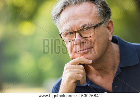 Close up face of satisfied senior man at park looking at camera. Portrait of mature man sitting in the park with hand on chin. Smiling old man in casual thinking outdoor.
