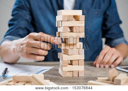 Businessman thinking about new challenge. Close up of hand of man taking a piece of building wooden bricks. Businessman trying to find a solution to problem. Risk and strategy concept.