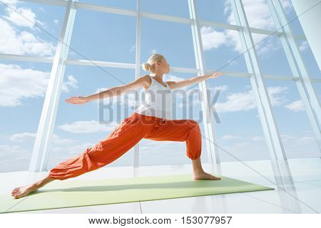 Young woman doing yoga indoors