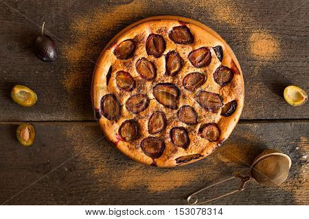 Plum cake on wooden rustic background. Overhead view