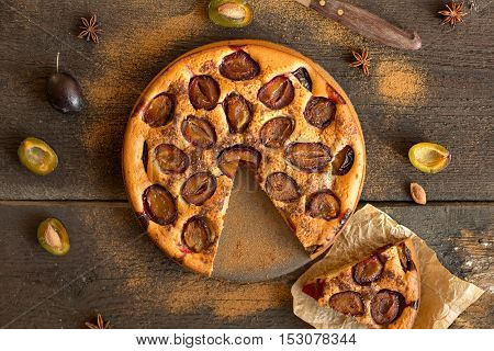 Plum cake on wooden rustic background.Eyes bird view