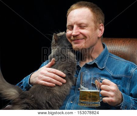 Happy Man With A Mug Of Beer And Cat In The Chair. Black Background