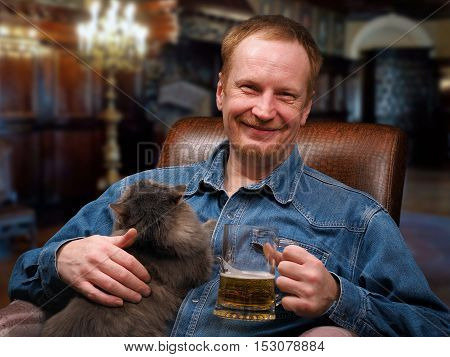 Happy man with a mug of beer and cat in the chair.