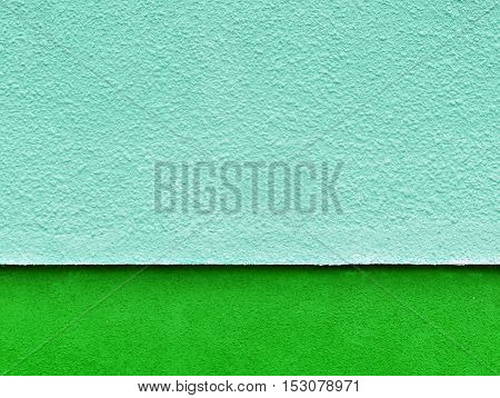 Architectural background. Blue plaster wall texture with a green stripe at the bottom. Place for an inscription.