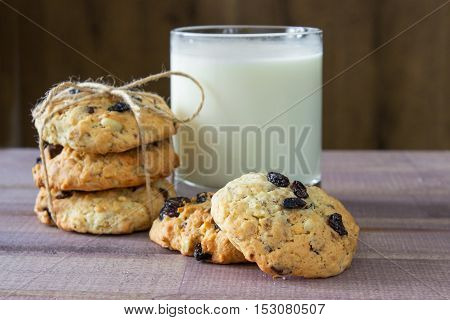 Closeup of pile made from homemade moms chocolate cookies and glass of milk on wooden background