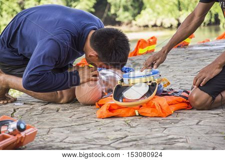 CPR and AED training child dummy drowning case select focus a man help breathing Kanchanaburi Thailand 21-22 October,2016