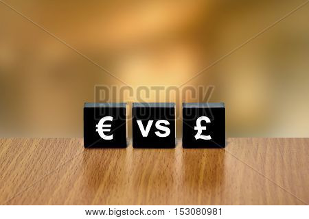 euro versus pound currency on black block with blurred background