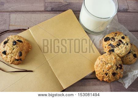 Closeup of homemade moms chocolate cookies with glass of milk and vintage notebook on wooden background