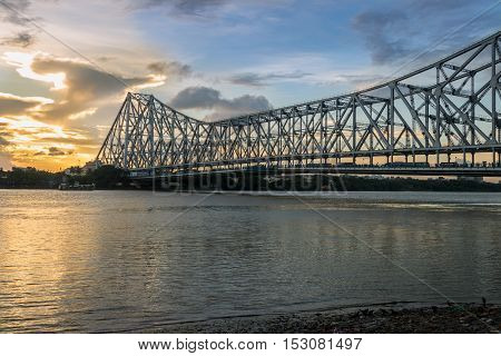 Howrah Bridge on river Hooghly at sunset. Howrah Bridge is a cantilever bridge with a suspended span over the Hooghly River in West Bengal, India.