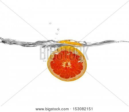 Grapefruit falling into water on white background