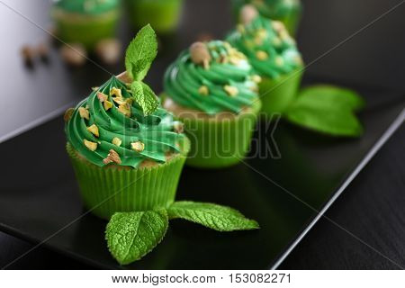 Pistachio cupcakes with mint leaves on plate