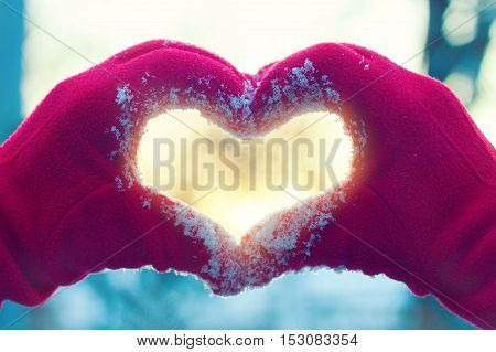 Woman hands in winter gloves heart symbol shaped lifestyle and feelings concept with sunset light winter nature on background. Heart symbol made with two hands. Woman's hands in red gloves on winter natural background. Valentine's Day