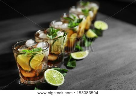 Glasses of cocktail with ice, lime and mint on dark textured background