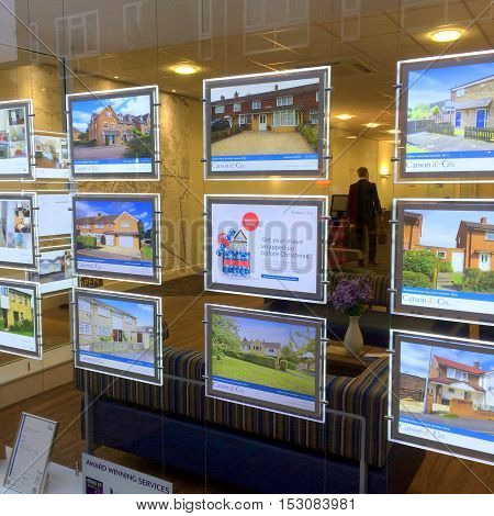 Bracknell,England - October 24, 2016: Houses and property for sale in the window of Carson & Co, an estate agents in Bracknell Town Center in the south of England. A person can be seen in the office