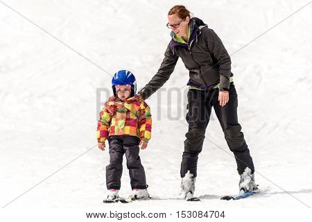 Professional ski instructor is teaching a child to ski on a sunny day on a mountain resort with sun and snow. Family and children active vacation.