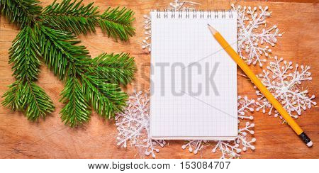 Pencil And Notepad On Old Rustic Table Decorated With A Fir Branch.