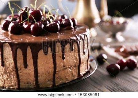 Delicious cake with cherry on table