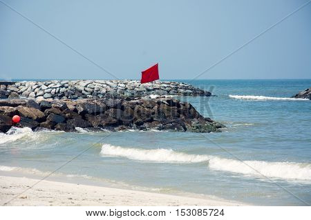 stormy sea, the red flag on the beach of the Persian Gulf