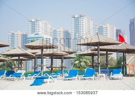 Dubai skyscrapers, palm, umbrella on the beach of the Persian Gulf