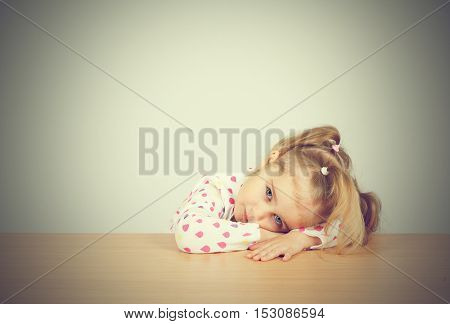 Little Girl Resting Head On Wooden Surface At Table.
