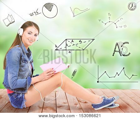Young woman with book sitting on wooden floor and listening to music against blurred background. Diversity of school icons on background.