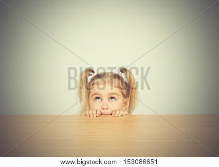 Little Girl In Casual Clothes Looking Up And Thinking