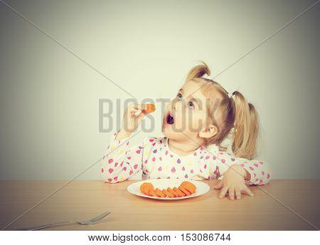 Little Girl Eats Carrot With Fork.