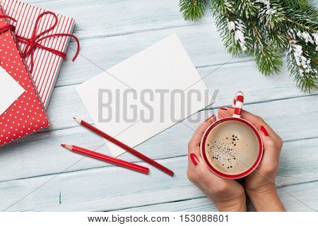 Xmas greeting card, female hands holding coffee cup, christmas gift boxes and snow fir tree above wooden table. Top view with copy space