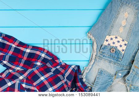 Set of women's clothes close up. Blue wooden background.
