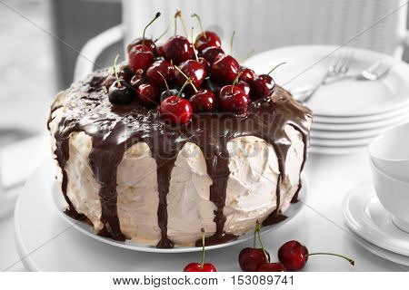 Cake with caramel and cherries on table