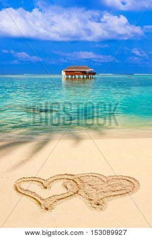 Drawing connected hearts on beach - concept holiday background