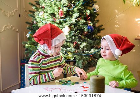 Kids brothers child boys making by hands x-mas decorations. smiling happy boys waiting christmas and Santa