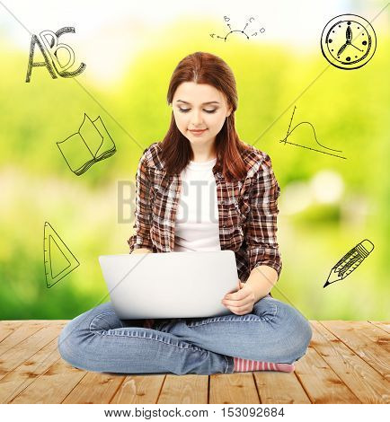 Young woman with laptop sitting on wooden floor against blurred background. Diversity of school icons on background.