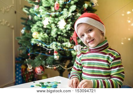 Kid child boy making by hands x-mas decorations. smiling happy boy waiting christmass and Santa